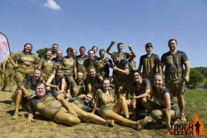 Group of people posing after tough mudder
